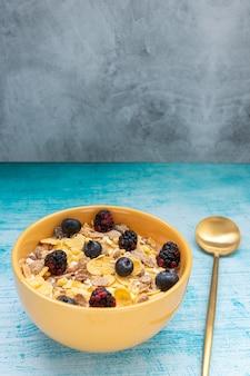 Petit-déjeuner avec des céréales granola et des fruits, comme des myrtilles et des mûres