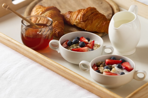 Petit déjeuner coloré savoureux avec de l'avoine, du yaourt, de la fraise, du myrtille, du miel et du lait sur fond blanc. petit déjeuner au lit. espace de copie. vue de dessus.