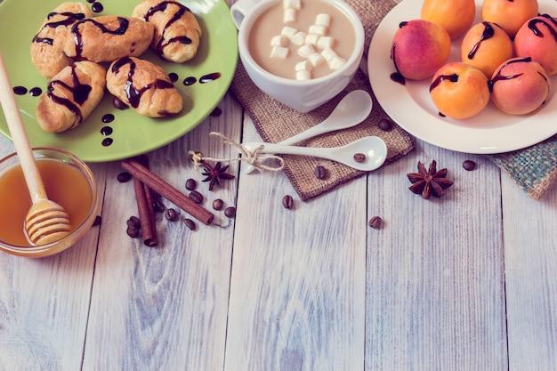 Petit déjeuner composé de café, croissants, abricots, miel, cannelle et anis