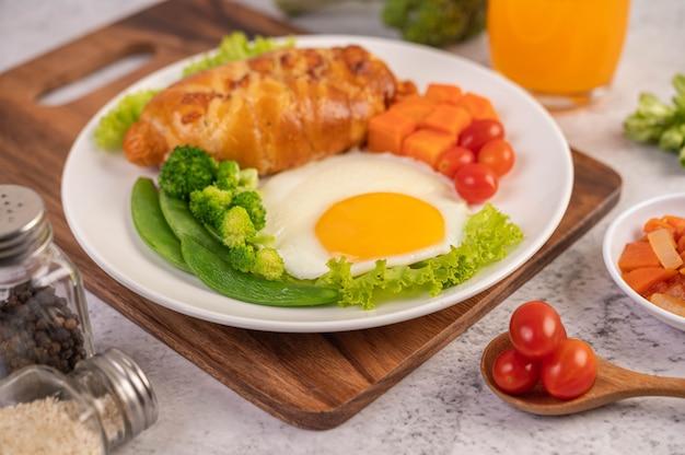 Petit déjeuner composé de pain, œufs au plat, brocoli, carottes, tomates et laitue sur une plaque blanche.