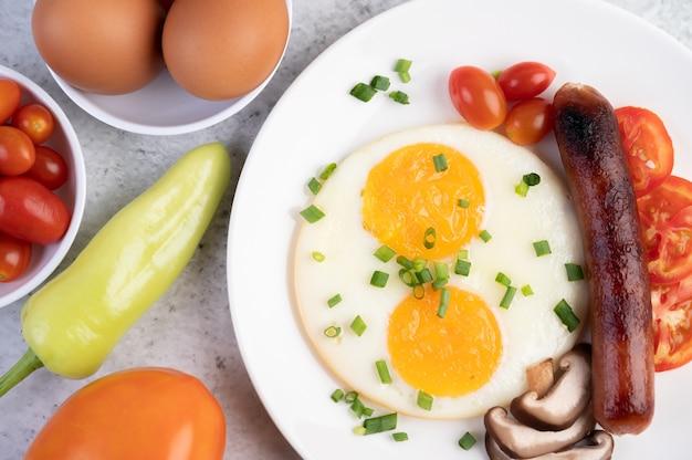 Petit déjeuner composé de pain, œufs au plat, tomates, saucisse chinoise et champignons.
