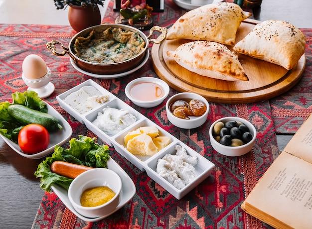 Petit déjeuner confiture miel beurre fromages fromages cottage saucisses oeufs légumes et pain d'air