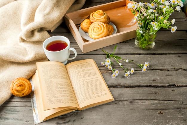 Petit-déjeuner confortable au printemps ou au début de l'automne, scones fraîchement sortis du four et bouquet de marguerites des champs et livre fascinant. espace copie