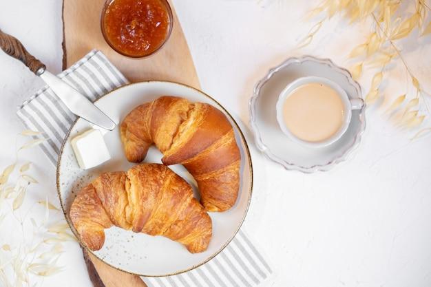 Petit déjeuner continental, une tasse de café avec du lait, deux croissants, du beurre et de la confiture d'orange sur une planche de bois, vue du dessus