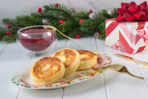 Petit-déjeuner crêpes au fromage et confiture de framboises sur fond de branches de sapin avec cônes et fruits rouges et un cadeau