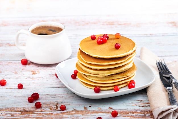 Le petit-déjeuner des crêpes aux canneberges sur une table en bois et une tasse de café.