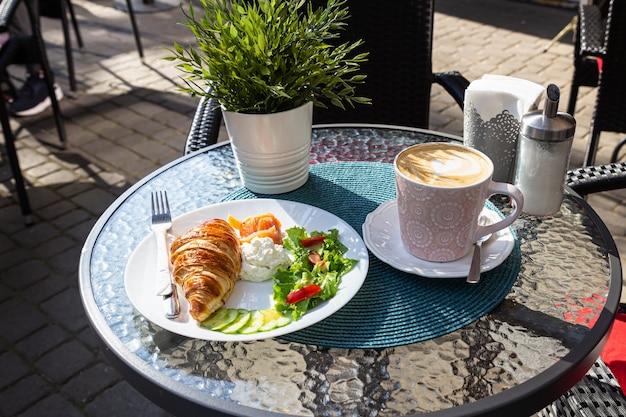 Petit-déjeuner avec croissant et cappuccino sur la table tôt le matin dans un café de la rue.