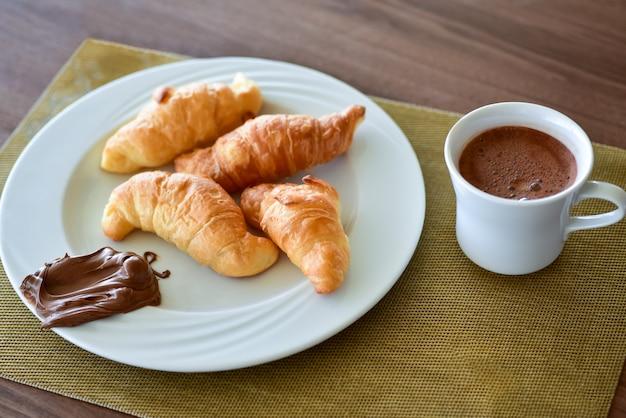 Petit-déjeuner croissant avec crème au chocolat sur une assiette.