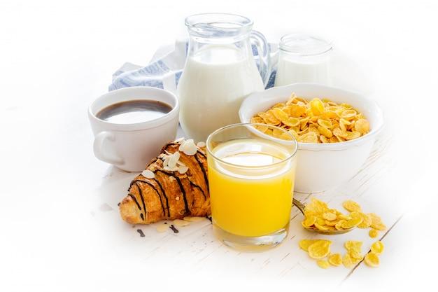 Petit-déjeuner avec croissant, jus de fruits, café et céréales