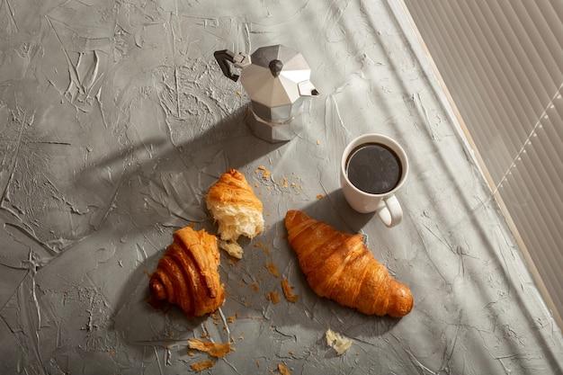 Petit-déjeuner avec croissant sur planche à découper et café noir. concept de repas du matin et petit-déjeuner.
