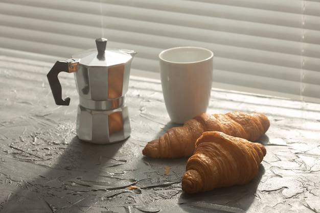 Petit-déjeuner avec croissant sur planche à découper et café noir. repas du matin et petit-déjeuner.