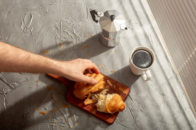Petit-déjeuner avec croissant sur planche à découper et café noir