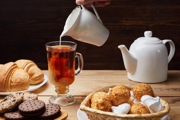 Petit-déjeuner avec des croissants, du lait, du thé et des bonbons sur une table en bois