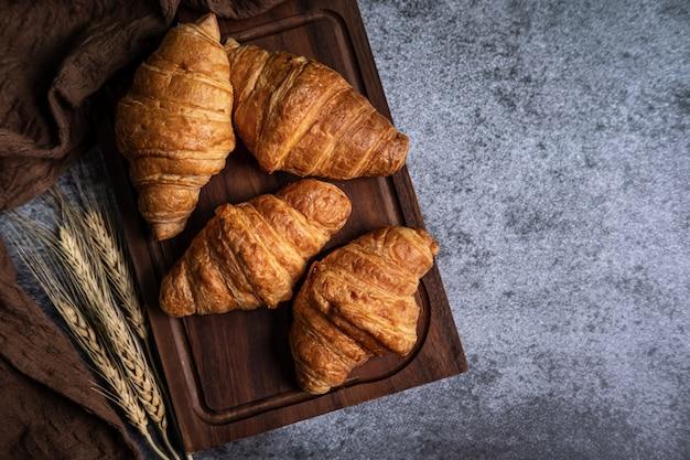 Petit déjeuner avec croissants frais sur planche de bois