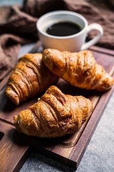 Petit déjeuner avec croissants frais et tasse de café noir sur planche de bois