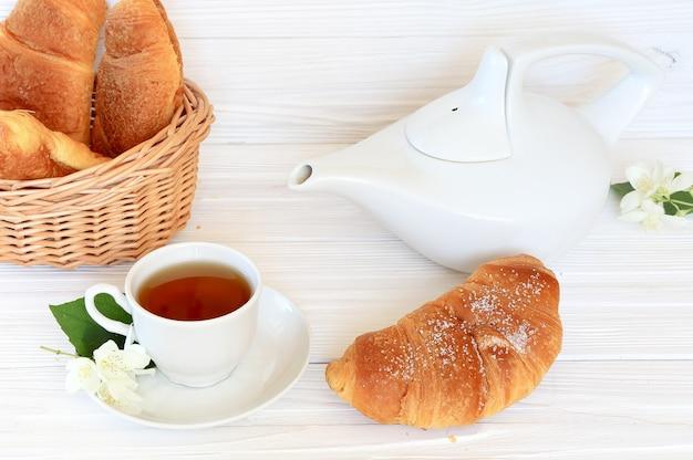 Petit-déjeuner - croissants et thé au jasmin sur un fond en bois clair