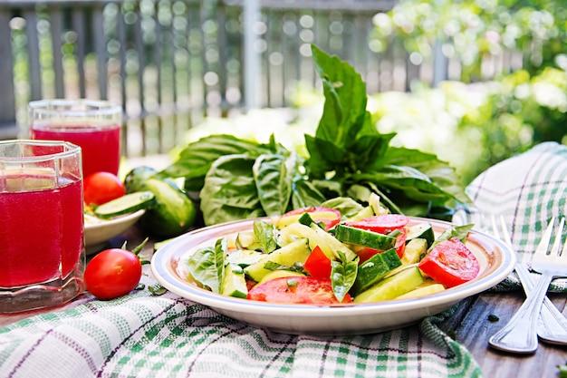 Petit déjeuner dans le jardin d'été. salade de tomates et concombres aux oignons verts et basilic.