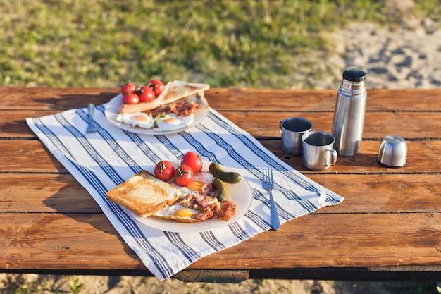 Petit-déjeuner dans la nature eggsufs au plat avec du pain grillé au bacon et du café chaud dans un thermos