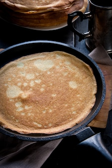 Petit déjeuner dans le style rustique: beaucoup de crêpes ou crêpes fraîchement cuites, arrosées de confiture et décorées de baies. dans le fond et une poêle à frire.
