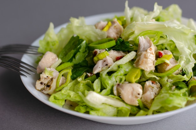 Petit déjeuner ou déjeuner sain. salade de légumes frais de laitue iceberg, poireaux et poitrine de poulet.