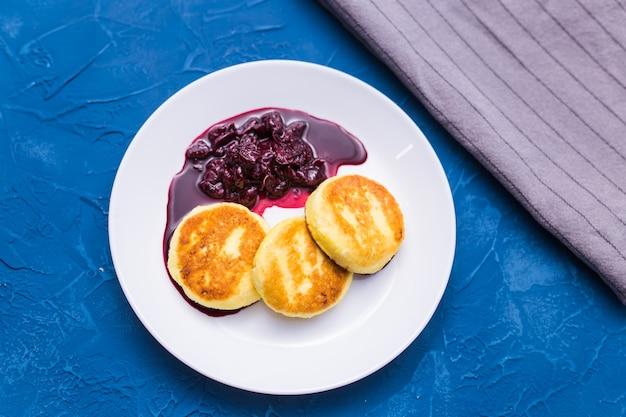 Petit déjeuner et délicieux concept - crêpes au fromage cottage avec de la confiture, mur bleu.