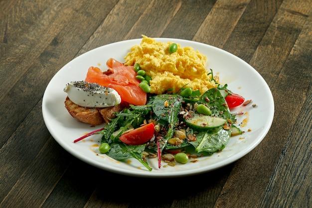 Petit-déjeuner délicieux et copieux - œufs brouillés et toasts au fromage à la crème et au saumon, mélangez la salade dans une assiette blanche sur une surface en bois