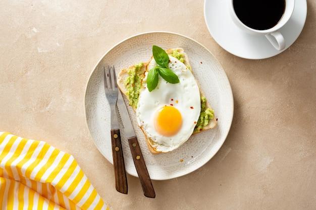 Petit déjeuner délicieux. toast à l'avocat et œuf au plat. alimentation saine, vue de dessus.
