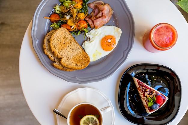Petit déjeuner avec dessert; smoothie et thé sur une table ronde blanche