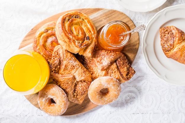 Petit déjeuner avec différentes pâtisseries françaises, jus et confiture