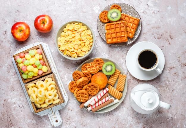Petit déjeuner avec divers bonbons, gaufrettes, flocons de maïs et une tasse de café, vue du dessus