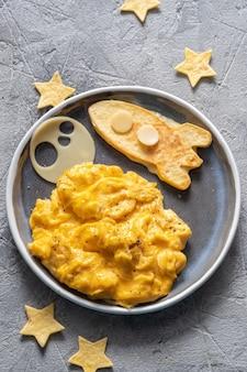 Petit-déjeuner drôle pour enfants avec œufs brouillés, fromage et fusée spatiale tortilla