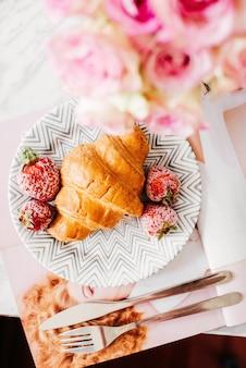 Petit déjeuner du croissant sur la table avec une fourchette et un couteau et un bouquet coloré