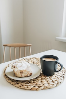 Petit-déjeuner du matin avec café au lait et dessert sur table blanche