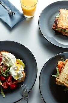 Petit-déjeuner du matin - nombreux sandwichs, œufs bénédictins, bacon, jus d'orange et légumes