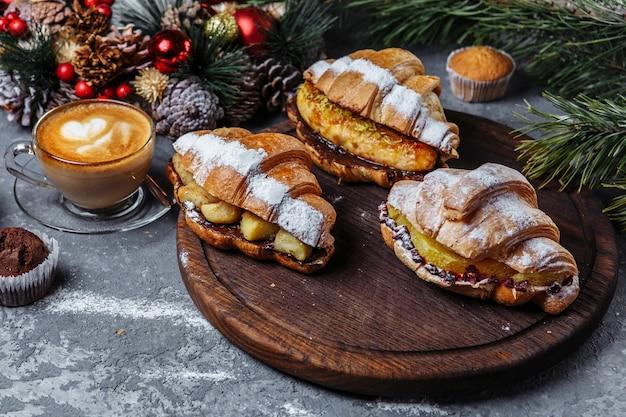 Petit-déjeuner du nouvel an avec des croissants. ensemble de trois croissants du nouvel an. croissants du nouvel an à la banane caramélisée, à l'orange et à l'ananas.