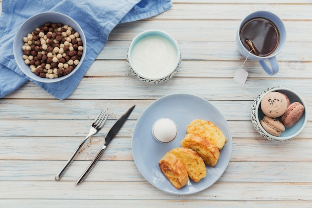 Petit-déjeuner avec du yogourt aux croûtons frits et du thé noir sur une surface en bois clair