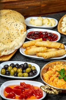 Petit déjeuner ensemble oeufs tomates olives pain vue latérale