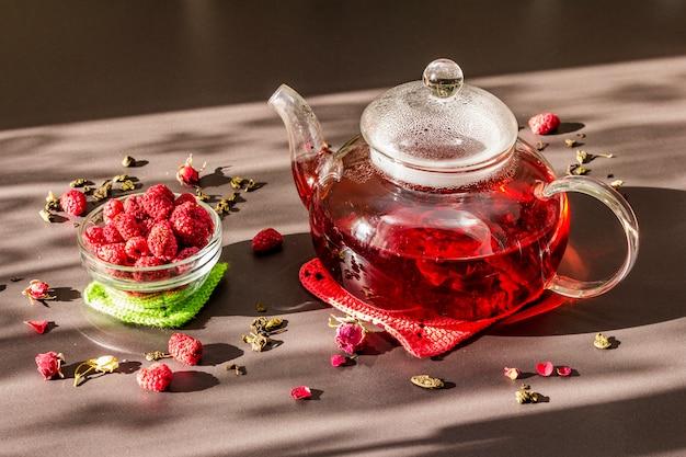 Petit déjeuner ensoleillé. thé vert framboise sucré dans une bouilloire en verre avec des fruits secs, des fleurs et des feuilles