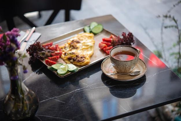 Petit déjeuner d'été au café. oeufs au plat avec des légumes frais et une tasse de thé
