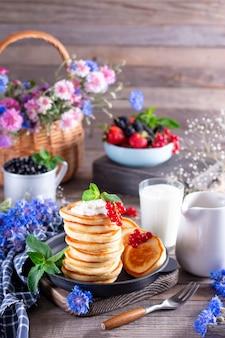 Petit-déjeuner d'été sain, crêpes maison avec baies fraîches et crème sure sur une table en bois