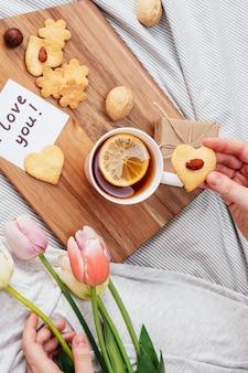 Petit déjeuner festif au lit pour la saint-valentin. thé et biscuits de vos propres mains en forme de cœur. une note sur papier, un cadeau et des fleurs à votre fille bien-aimée.