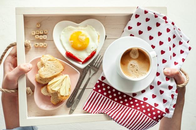 Petit-déjeuner de la fête des mères. plateau il y a une tasse de café deux assiettes d'oeufs brouillés et du pain en forme de cœur et l'inscription je t'aime maman vue d'en haut