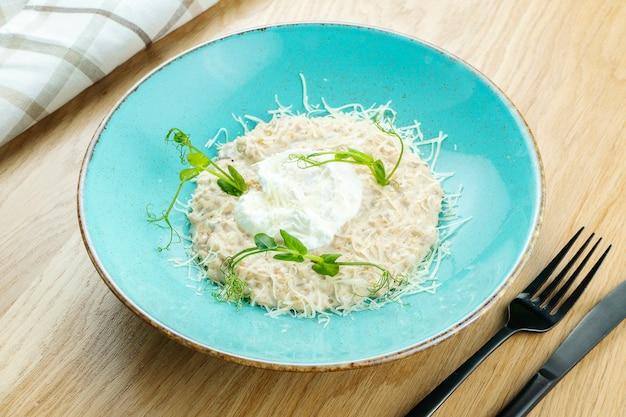 Petit déjeuner. flocons d'avoine au parmesan et œuf poché dans un bol bleu sur un fond en bois.