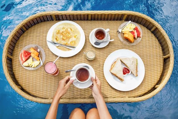 Petit déjeuner flottant dans la piscine. plateau de paille avec des aliments différents.