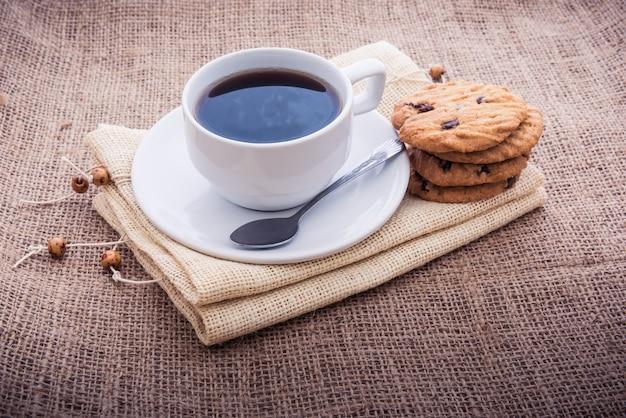 Petit-déjeuner frais, café chaud et cupcakes sur des serviettes dans un style rétro.