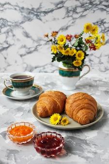 Petit déjeuner français avec croissants, confiture d'abricot, confiture de cerise et une tasse de thé, fleurs rouges et jaunes