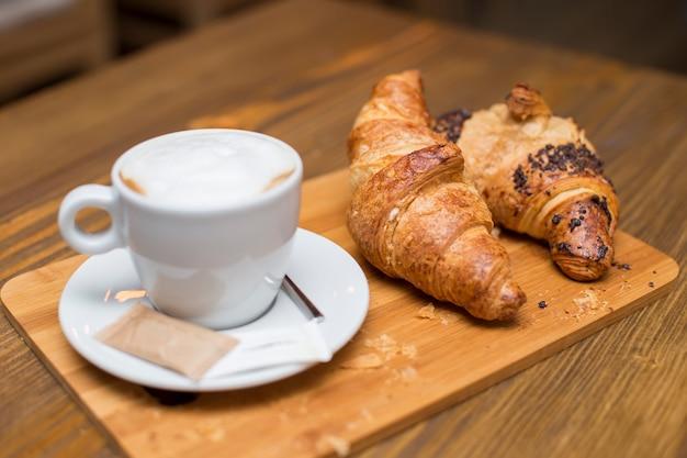 Petit déjeuner français traditionnel avec des tasses de café chaud et de délicieux croissants frais placés sur une table vintage
