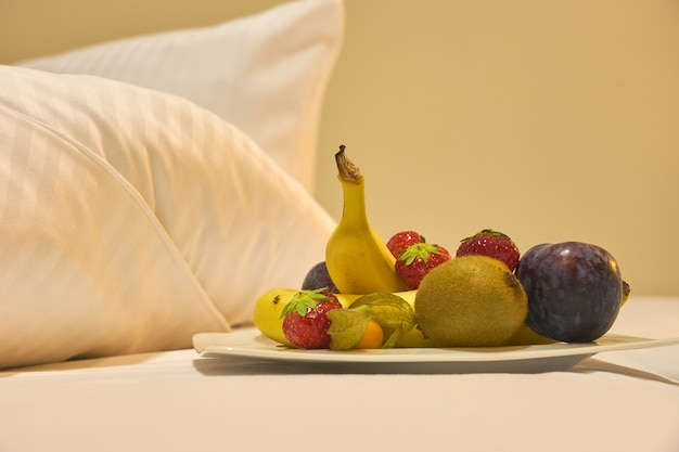 Petit-déjeuner de fruits et de baies au lit.