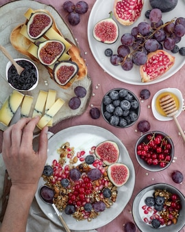 Petit-déjeuner avec fruits, fromage, yaourt, muesli et confiture