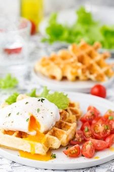 Petit déjeuner avec gaufres au fromage, œuf poché et tomates cerises. nourriture saine